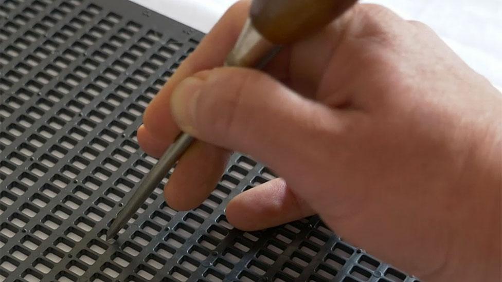 Las herramientas: una rejilla sobre el papel y una lezna, para marcar los puntos necesarios