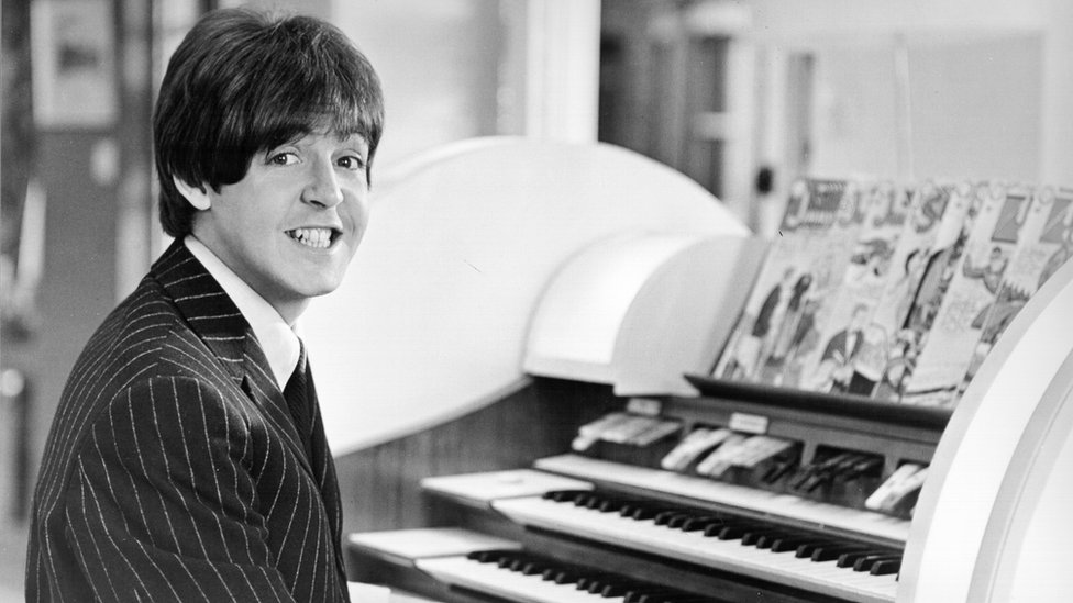 McCartney sonriendo sentado al piano.