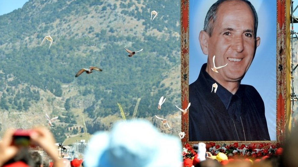 """A portrait of Father Giuseppe """"Pino"""" Puglisi, an outspoken anti-Mafia advocate, hangs over about crowd during his beatification ceremony in Palermo on May 25, 2013."""