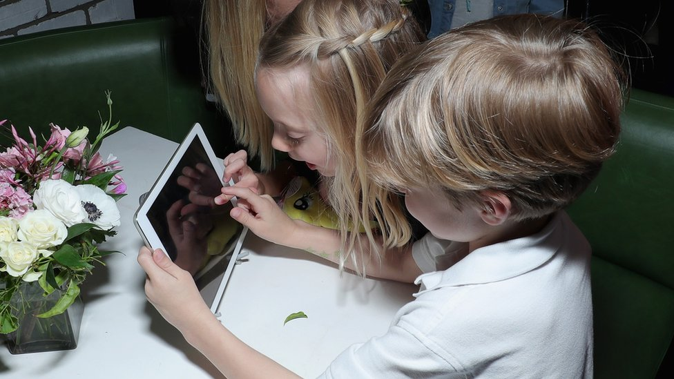 A little boy and girl play with a tablet