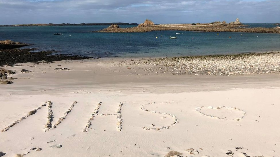 """NHS"" drawn on beach"