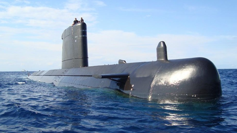A submarine floats on the water's surface, as two people can be seen sitting on its vertical fin
