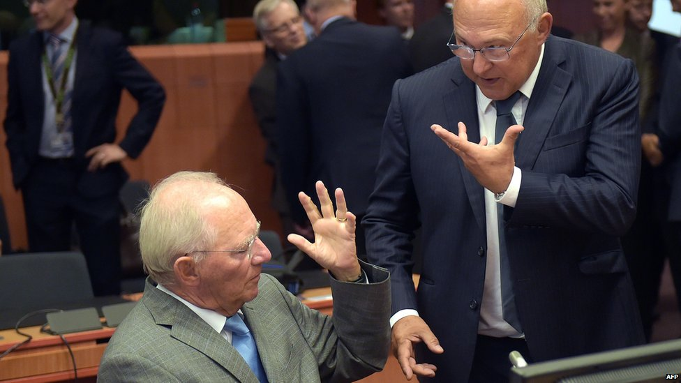 German Finance Minister Wolfgang Schaeuble (left) and French Finance Minister Michel Sapin gesture as they attend an extraordinary Eurogroup meeting on Greece at the European Council in Brussels, 14 August 2015