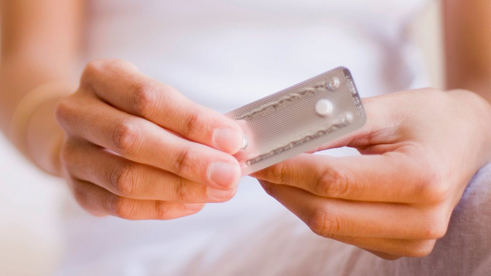 Woman holding the morning after pill