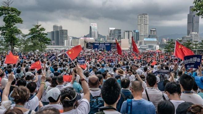 Para demonstran mengibarkan bendera China dalam aksi unjuk rasa di Taman Tamar, Hong Kong