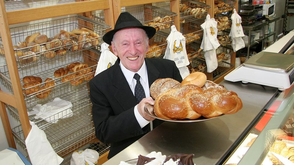 Mendel Glick holds a plate of bagels and other baked items behind the counter at Glick's