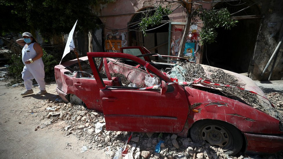 A woman walks past a damaged car following the explosion in Beirut's port area (9 August 2020)