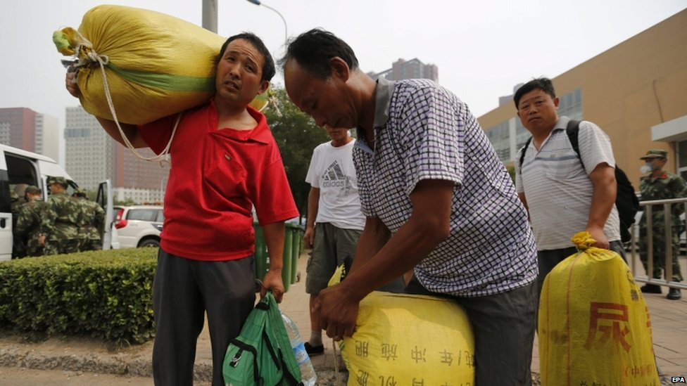 Evacuees carry luggage - 15 August