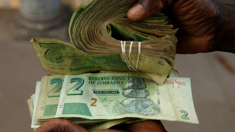 A vendor in Harare with new old $2 bond notes and new $2 Zimbabwean notes in November - Zimbabwe