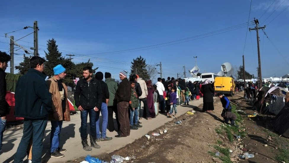 Migrants and refugees queue for food as they wait to cross the Greece-Macedonia border near the village of Idomeni (02 March 2016)