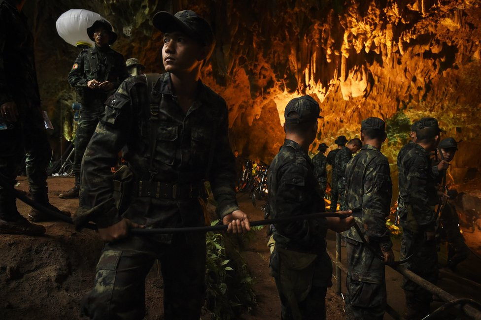 Soldiers hold an electric cable in a cave