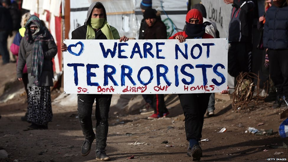Two migrants hold a sign that says: We are not terrorists so don't destroy our homes