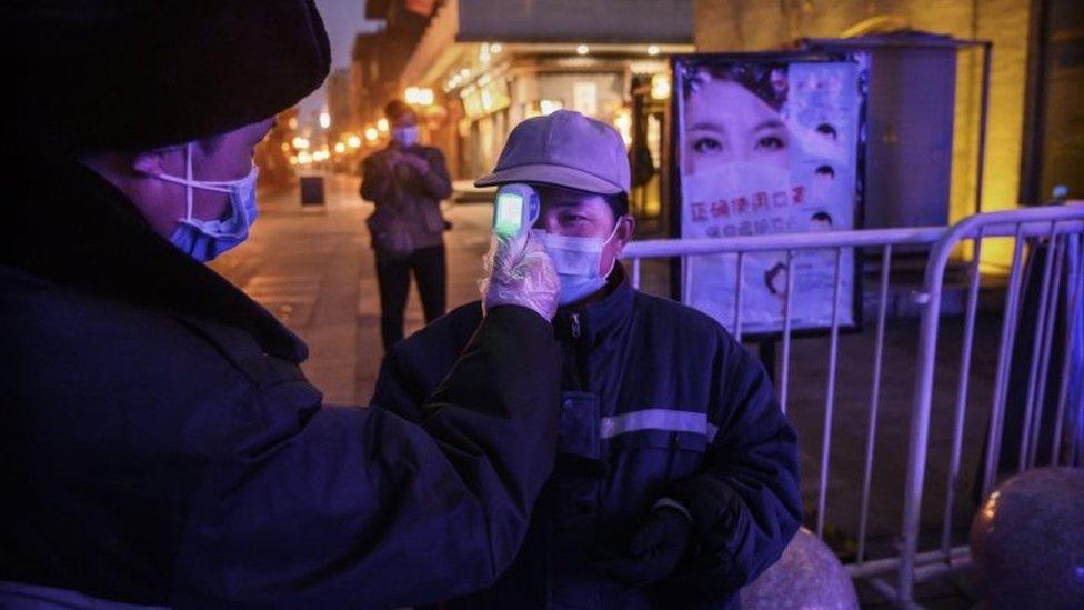 Un trabajador chino con una mascarilla registra la temperatura de un colega en Pekín, 12 de febrero, 2020