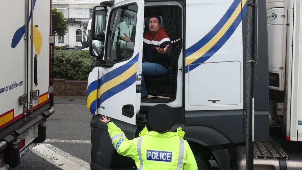 A police officer talks to an exasperated lorry driver outside the Port of Dover in Kent on Monday