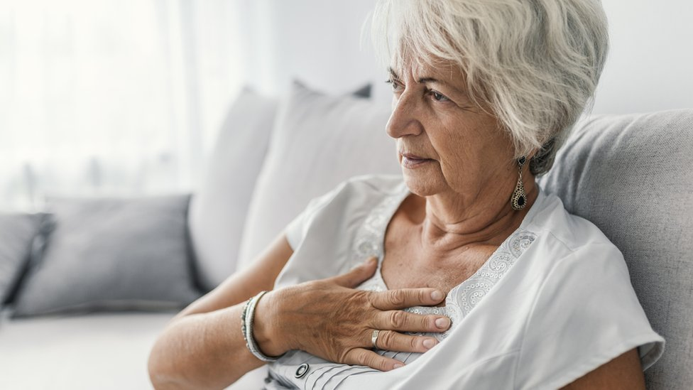 Older woman clutching her heart