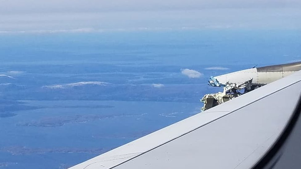 A view over the wing, showing land in the distance beyond, while the plane is still airborne. Mangled metal can be seen poking above the surface.