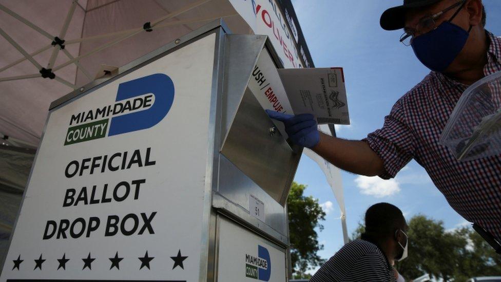 Un hombre con mascarilla inserta su voto en un buzón del correo para las elecciones en Estados Unidos.