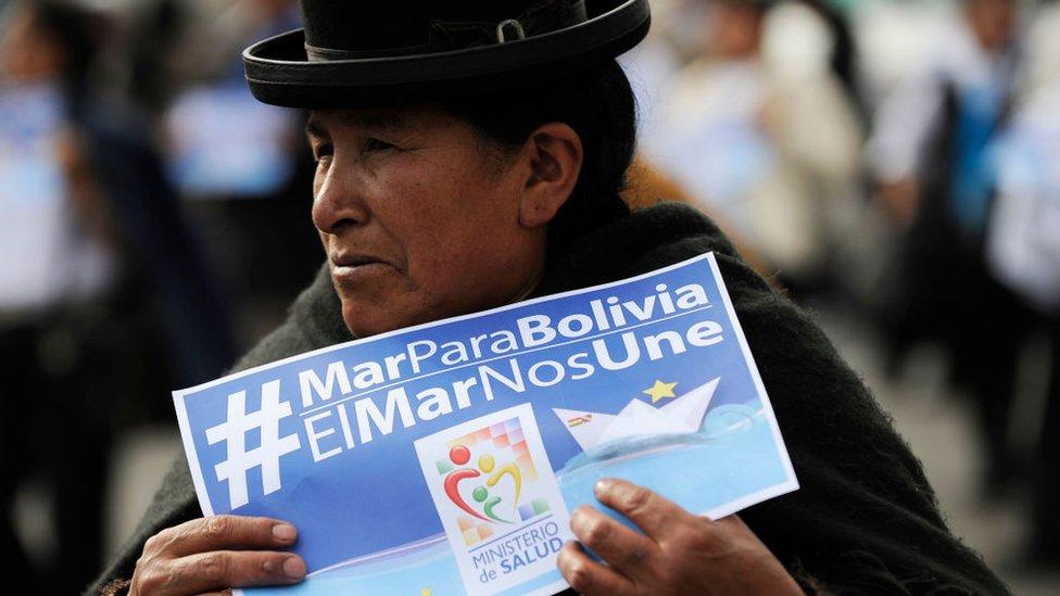 "Mujer boliviana sujeta un cartel que dice ""Mar para Bolivia""."