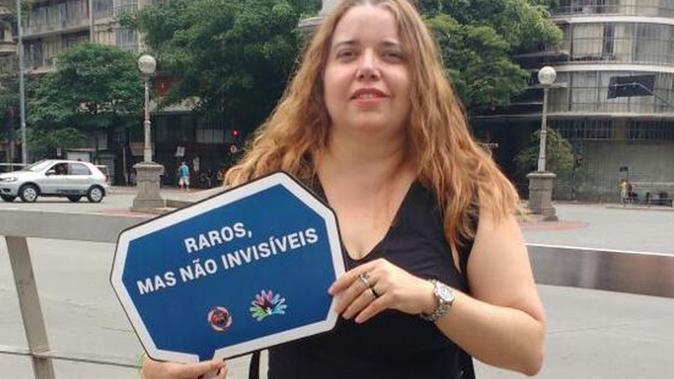 Margareth na rua, sorrindo e com placa na mão que diz: 'Raros, mas não invisíveis'