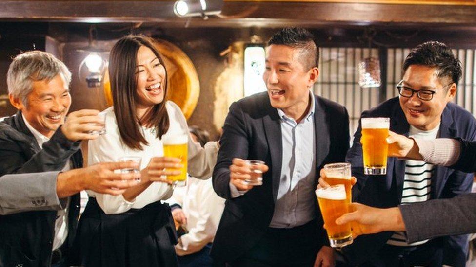 Un grupo de japoneses brinda con cerveza en un restaurante.