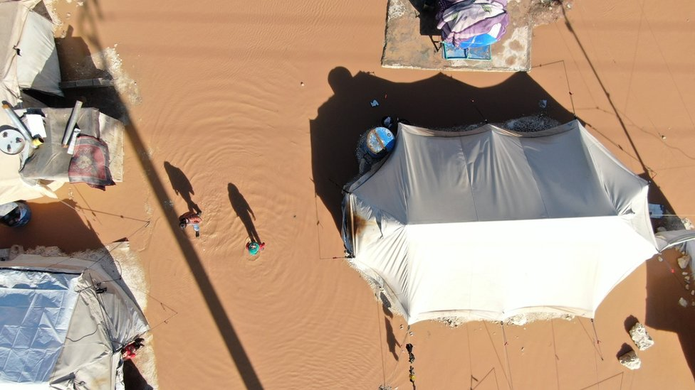 A girl and a boy stand next to their flooded tent at a camp in northern Idlib province, Syria