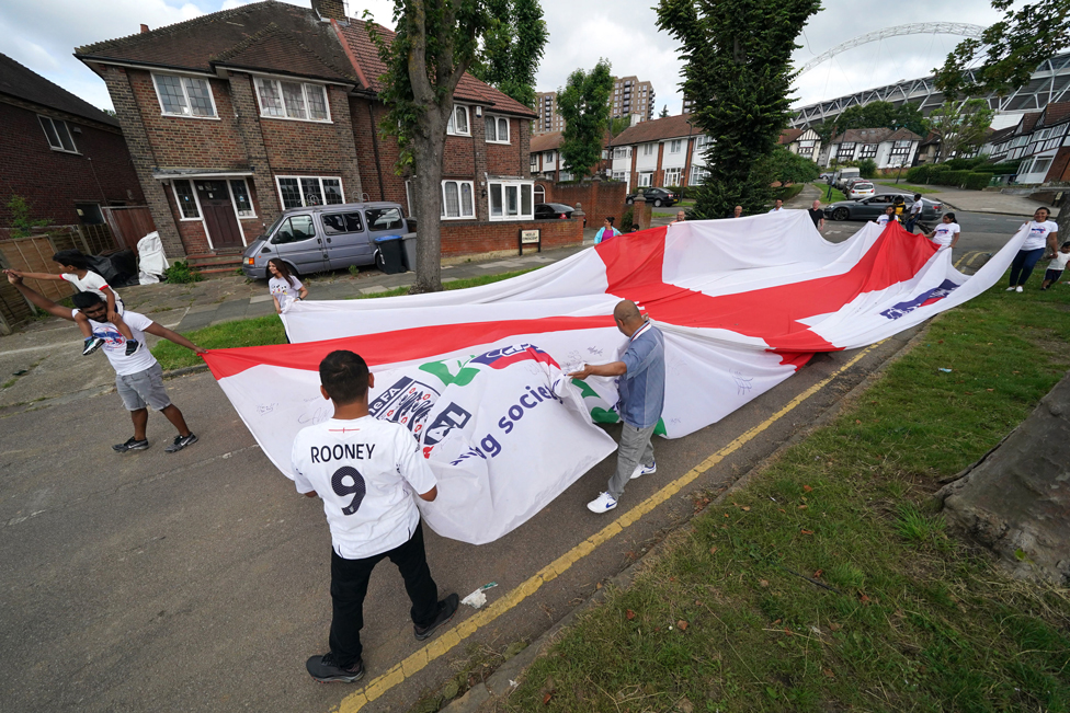 Local residents carry a giant England flag from Neeld Crescent in Brent, where Raheem Sterling grew up, on their way to Wembley Stadium