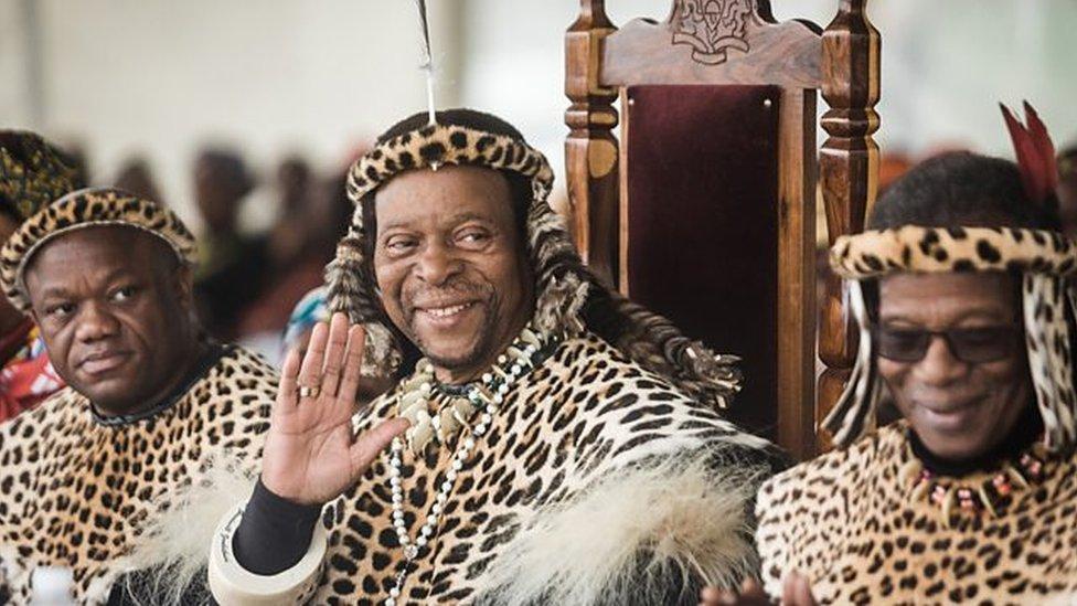 Rei Zwelithini acena em uma cerimônia, sentado e vestido com roupas tradicionais
