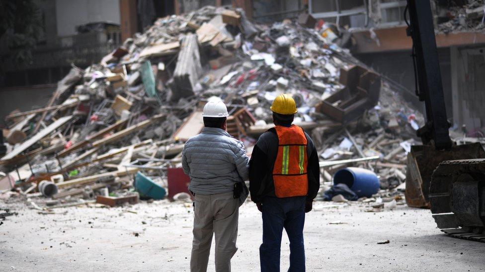 Two men with their backs turned to camera survey a pile of rubble