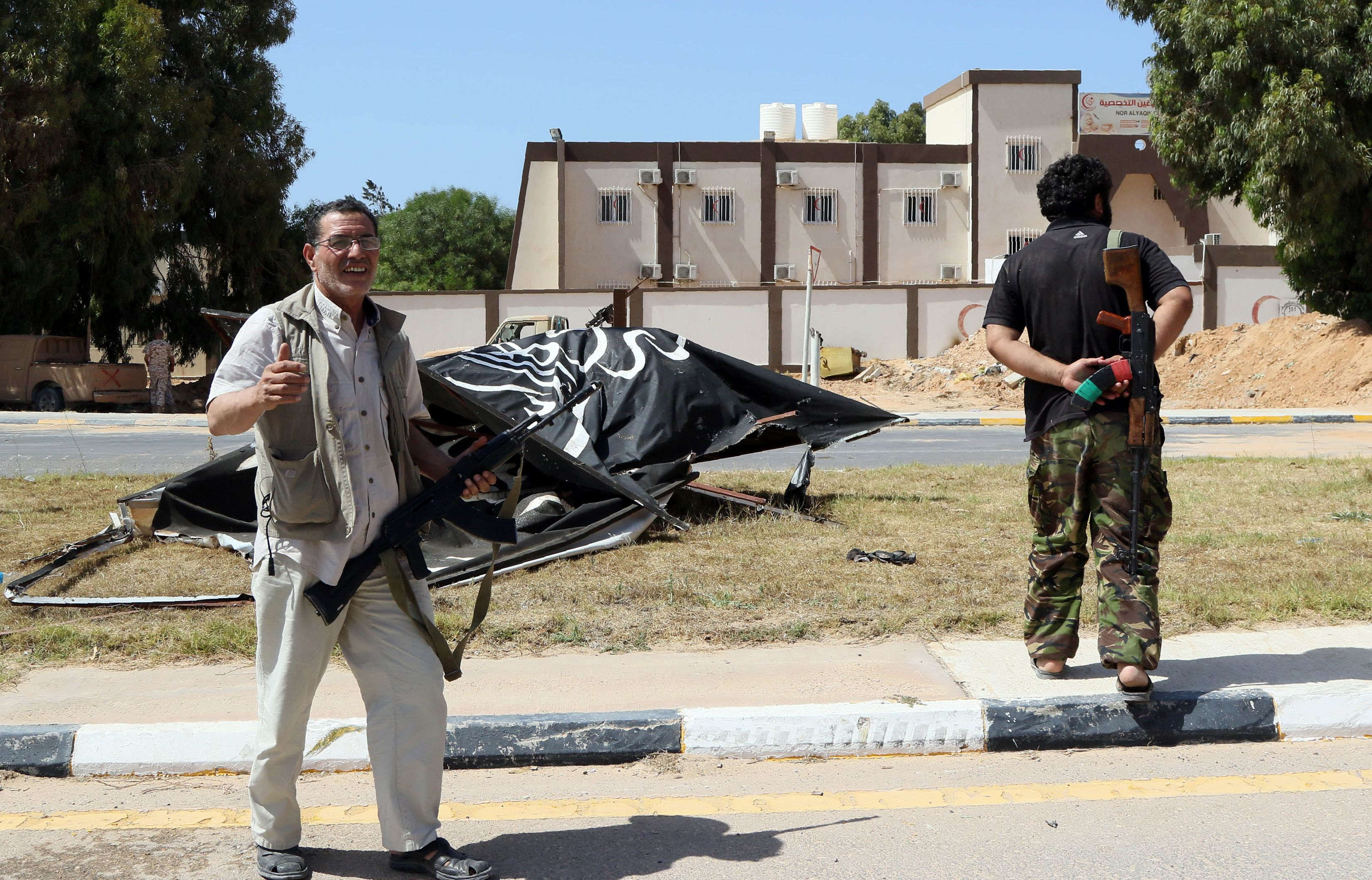man cheering in front of IS sign in Sirte, June 10 2016