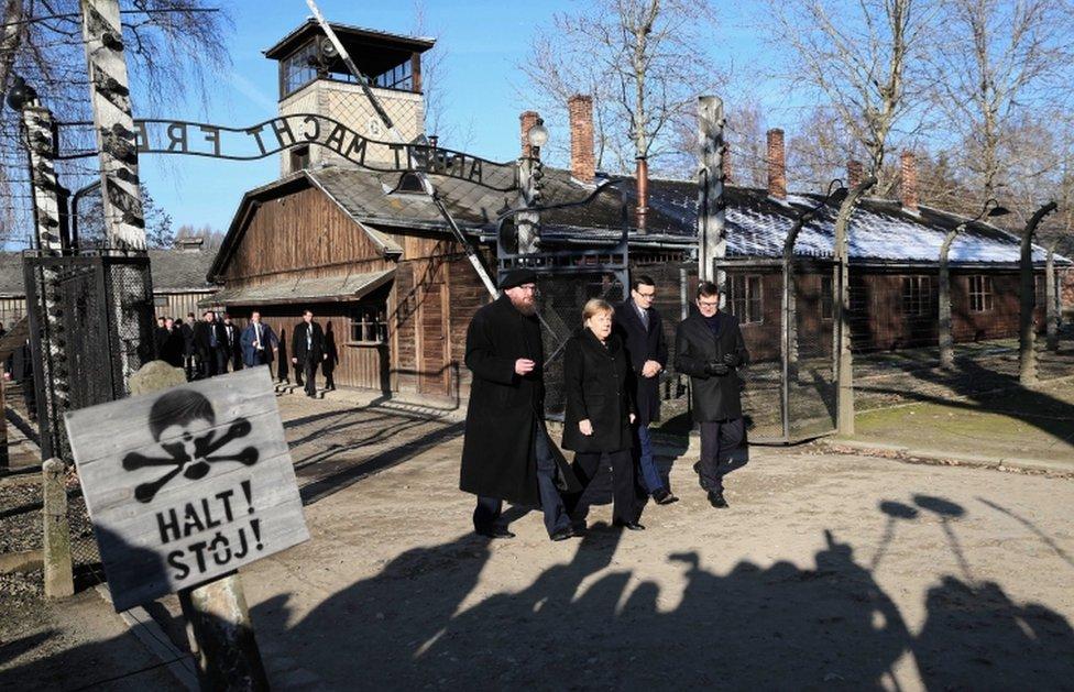 German Chancellor Angela Merkel walks through the gates of the Auschwitz-Birkenau Memorial and Museum, accompanied by Polish Prime Minister Mateusz Morawiecki