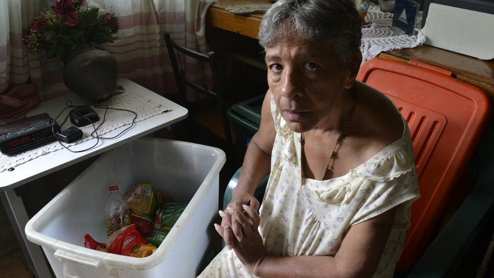 Norma Mújica next to a government food box