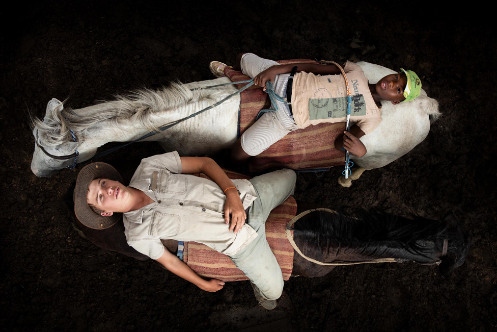 Aerial view of two young people lying on the backs of horses