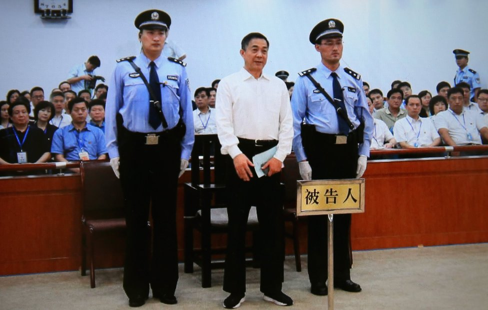 A screen shows the sentence of Chinese politician Bo Xilai (centre, flanked by security guards and with court attendees behind) on 22 September 2013 in Beijing, China.