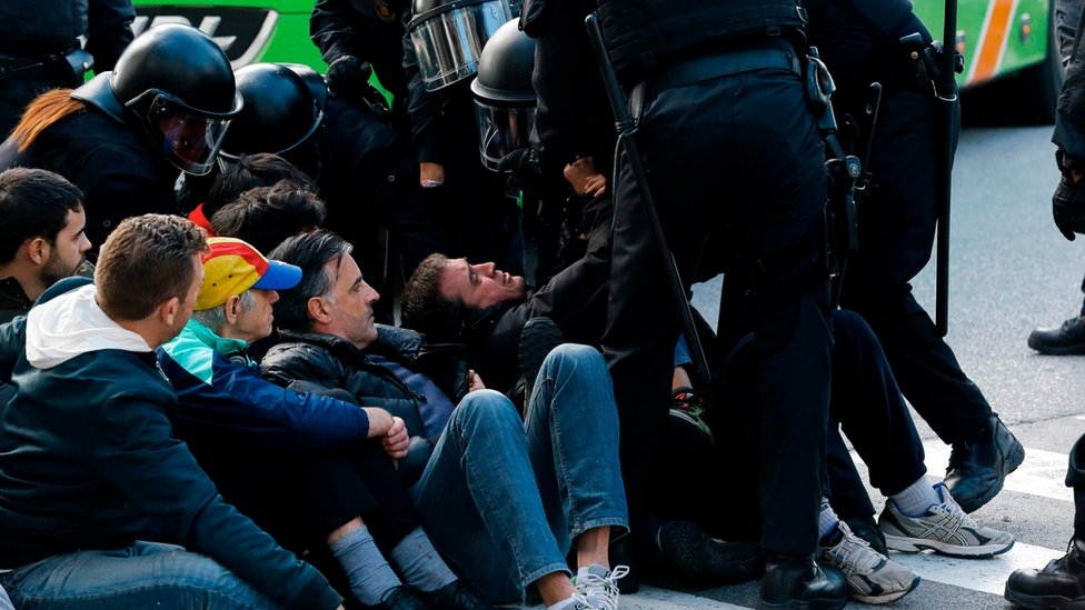 """Catalan regional policemen (Mossos d""""Esquadra) drag a picketer blocking the street at the North Bus Station in Barcelona"""