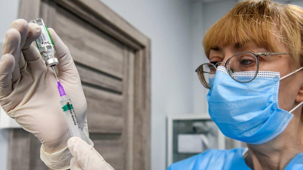 Profissional de máscara e óculos prepara dose da AstraZeneca