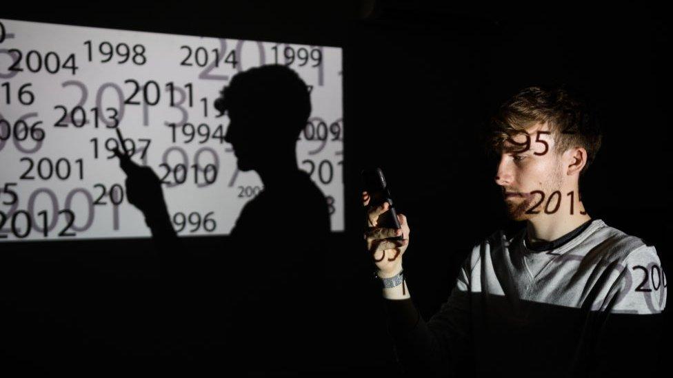 Čovek drži mobilni telefon u mraku