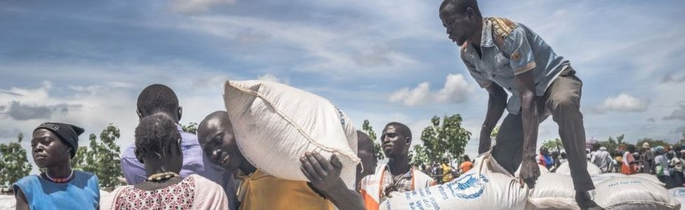 South Sudanese refugees seen collecting cassava flour provided by the World Food Program at the refugee settlement