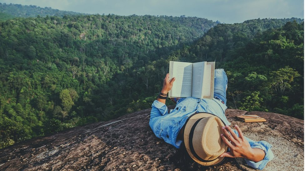 Young man relaxing and reading a book at the top of a rocky cliff, on holiday in Thailand.