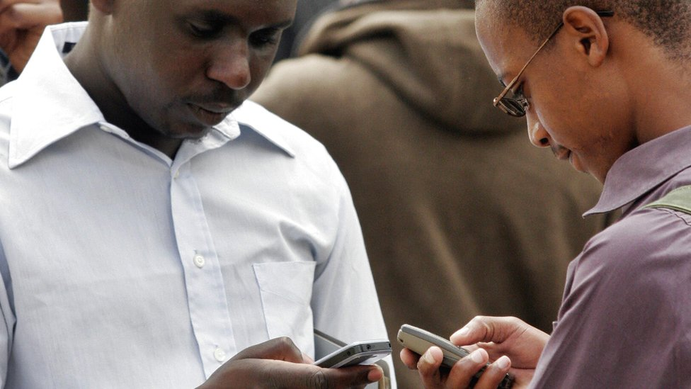 Two Kenyans texting on their phones - archive shot