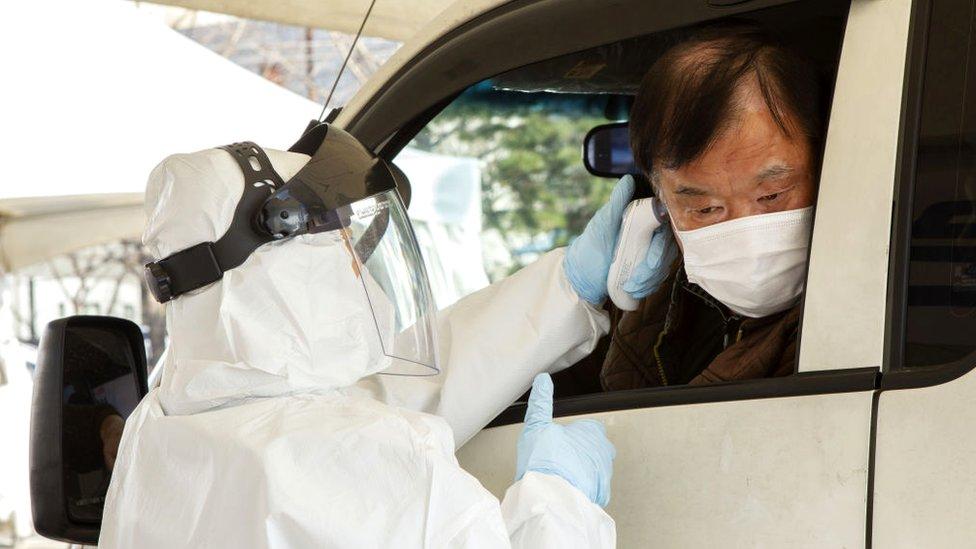 Un hombre pasando una prueba de covid-19 en su auto en febrero.