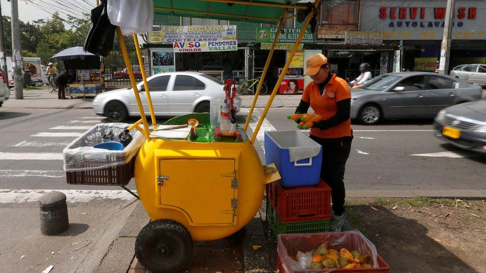 Mujer vendiendo jugo de frutas en Colombia