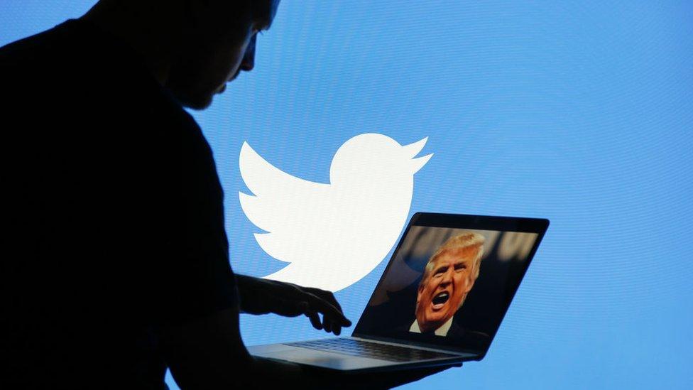 Una persona sujeta una computadora con la imagen de Donald Trump.