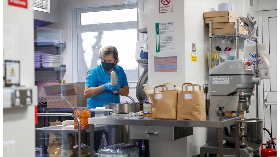 Woman in face mask preparing meals for children on free school dinners in lockdown, Milton Keynes