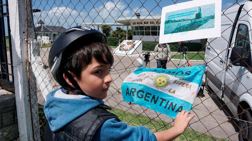 Niño con una bandera argentina y una foto del submarino