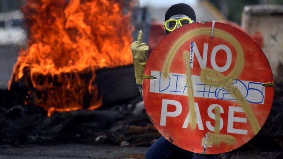 Un manifestante en las protestas en Cali con fuego detrás.