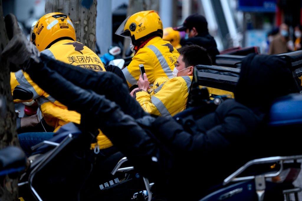 Motociclistas que hacen despachos a domicilio esperan a que les lleguen los pedidos en una calle en Shanghái