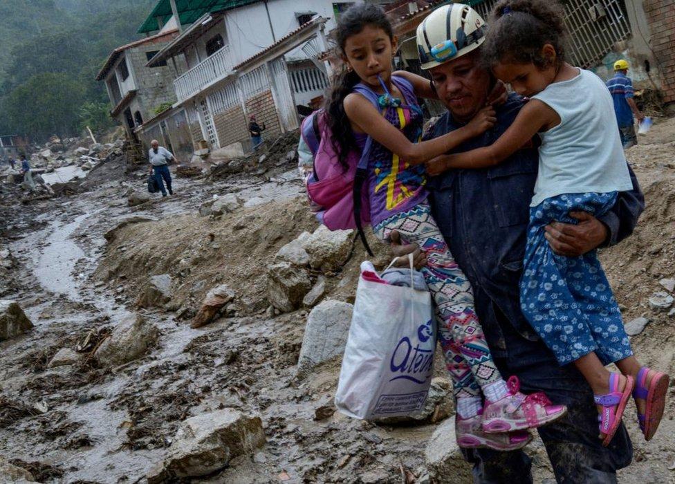 Rescatista con dos niñas en Tovar, Mérida, Venezuela.