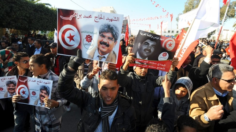 Tunisians, carrying portraits of assassinated opposition figure Mohamed Brahmi, gather to mark the third anniversary of the uprising that toppled deposed president Zine El Abidine Ben Ali