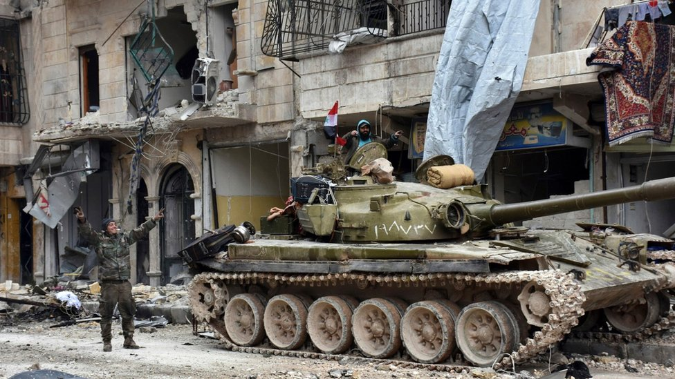 Syrian army soldiers make victory signs in the Sukkari district of Aleppo, Syria (23 December 2016)