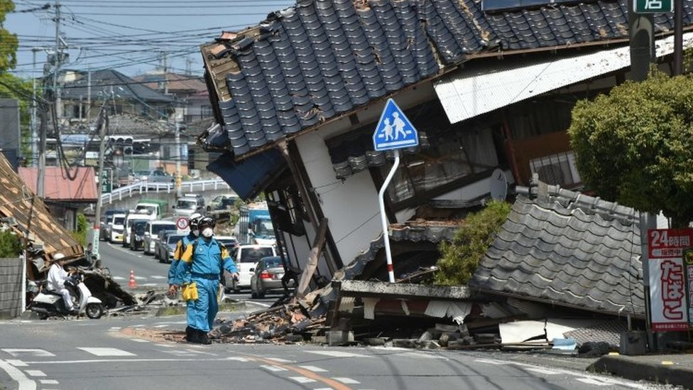 Policemen search for missing people in a damaged neighbourhood following twin earthquakes in Mashiki, Kumamoto prefecture (17 April 2016)